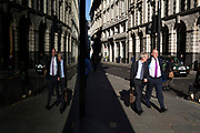 Reflected light as City workers pass by in the City of London, England, United Kingdom.