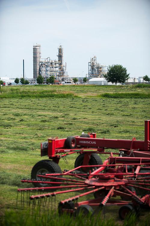 Nederland, Delfzijl, 30 juni 2010.Landbouwgebied met industrie op de achtergrond. Boer maait grasland.Foto (c)  Michiel Wijnbergh
