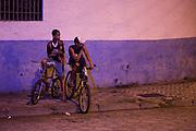 Two boys on bicyles listen to Cubatão Samba School