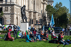 © Licensed to London News Pictures. 01/09/2020. London, UK. Members of Extinction Rebellion (XR) environmental campaign group gather in Parliament Square under the statue of Winston Churchill in central London with banners and flags as they start their sit-in this morning to blockade Parliament. XR plan to peacefully disrupt the UK Parliament with actions planned over two weeks, until MP's back the Climate Ecological Emergency Bill and prepare for crisis with a National Citizens's Assembly. Photo credit: Alex Lentati/LNP