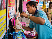 """17 FEBRUARY 2015 - BANGKOK, THAILAND: A man works on a client at a threading stand on Charoen Krung Road in Bangkok's Chinatown. About a dozen people, mostly women, have set up shop on the sidewalk to do hair removal for clients. They use thread to remove hair, a practice called """"threading"""" which originated in India more than 6,000 years ago. It's growing in popularity in the US and Europe as an alternative to waxing. A cotton or polyester thread is pulled along unwanted hair in a twisting motion, the hair is trapped in a mini lasso, and lifted out of the follicle.    PHOTO BY JACK KURTZ"""