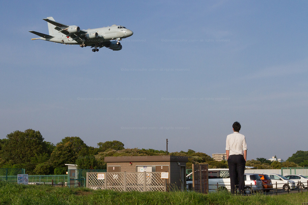 A man watches a Kawasaki P1 Maritime patrol aircraft with the Japanese Maritime Self Defence Force (JMSDF) landing at Atsugi  Airbase from a park in Yamato, Kanagawa, Japan. Tuesday May 1st 2018