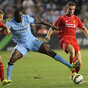 Yaya Touré, (centre), Manchester City, is challenged by Lucas Leiva, (left) and Jordan Henderson , Liverpool, during the Manchester City Vs Liverpool FC Guinness International Champions Cup match at Yankee Stadium, The Bronx, New York, USA. 30th July 2014. Photo Tim Clayton