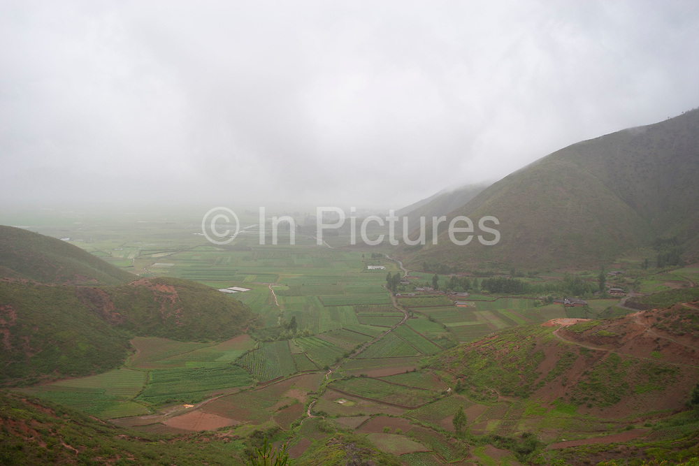 Landscape in the shadow of Shi Zi Shan, or Lion Mountain, near the small settlement of Li Ge on Lugu Lake, Yunnan, China. Crops which have to thrive in the iron rich red soil which erodes all around due to high precipitation levels.