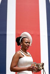 A fashionable racegoer poses for photographers during day five of Royal Ascot at Ascot Racecourse.