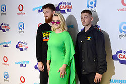 Jack Patterson (left), Grace Chatto and Luke Patterson (right) of Clean Bandit on the red carpet of the media run at Capital's Summertime Ball with Vodafone at Wembley Stadium, London.