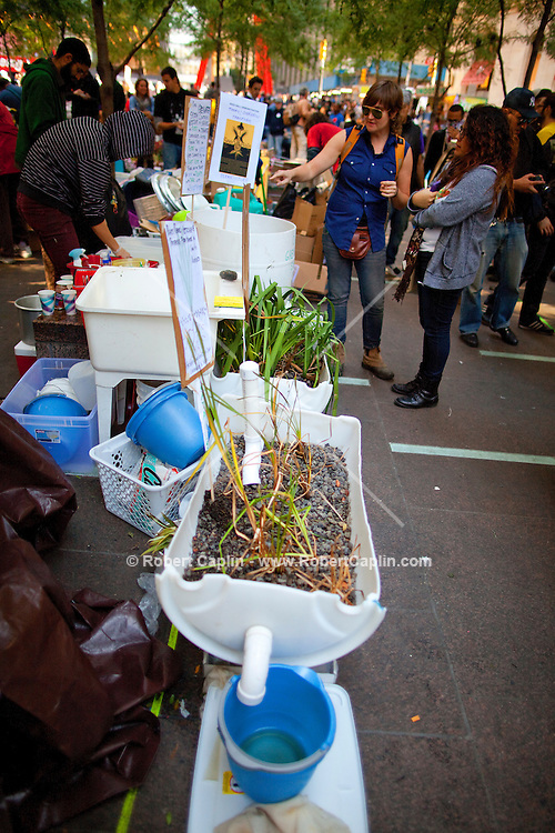 A water filtration system claiming to use plants to filter dish water is used in the make-shift food station in Zuccotti Park during the  Occupy Wall Street Protest in New York...Photo by Robert Caplin.