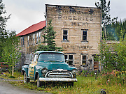 A green truck with yellow door parks next to the old Watsjold Groceries & Meat building (also labeled HARDWARE and GENERAL MERCHANDISE) in historic McCarthy. McCarthy and nearby Kennecott Mines National Historic Landmark are nestled under the glacier-clad Wrangell Mountains within Wrangell-St. Elias National Park and Preserve, Alaska, USA. Old mine buildings, artifacts, and colorful history attract summer visitors. Remote McCarthy is connected to Chitina via the McCarthy Road spur of the Edgerton Highway. At the east end of McCarthy Road, visitors must park their vehicle and walk across the footbridge to McCarthy. From McCarthy, a privately-operated shuttle takes visitors 5 miles to Kennecott. After copper was discovered between the Kennicott Glacier and McCarthy Creek in 1900, the Kennecott town, mines, and Kennecott Mining Company were created and named after the adjacent glacier. Kennicott Glacier and River had previously been named after Robert Kennicott, a naturalist who explored in Alaska in the mid-1800s. The corporation and town stuck with a mistaken spelling of Kennecott with an e (instead of Kennicott with an i). Partly because alcoholic beverages and prostitution were forbidden in the company town of Kennecott, the neighboring town of McCarthy grew quickly to provide a bar, brothel, gymnasium, hospital, and school. The Copper River and Northwestern Railway reached McCarthy in 1911 to haul over 200 million dollars worth of ore 196 miles to the port of Cordova on Prince William Sound. By 1938, the world's richest concentration of copper ore was mostly gone, the town was mostly abandoned, and railroad service ended. In the 1970s the area began to draw young people for adventure and the big money of the Trans Alaska Pipeline project. Declaration of the huge Wrangell-St. Elias National Park in 1980 drew adventurous tourists who helped revive McCarthy with demand for needed services.