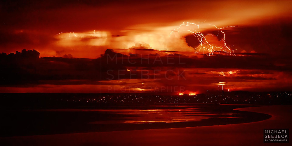 Lightning bolts discharge from a distant thunderstorm, while a bushfire burns on closer hills. Numerous smaller fires are burning throughout the hills in the wake of the bushfire.<br /> <br /> <br /> Code: BAWK0003<br /> <br /> Limited Edition of 125 Prints