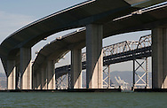 The eastern span of the San Francisco-Oakland Bay Bridge remains under construction with new lanes curving toward Oakland and Berkeley, Calif.,  on Saturday, Sept. 17, 2011.  The original eastern span, background, was damaged in the 1989 Loma Prieta earthquake. The new self-anchored suspension span is expected to open in 2013.  (© 2011 Cindi Christie/Cyanpixel Photography)