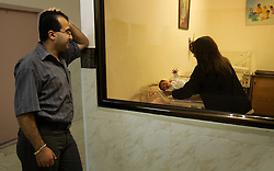 Wisam Kheir, watches as his newborn Mary is moved into the nursery at Al-Dibs Maternity Hospital in Bethlehem, Palestinian Territories, Nov. 14, 2004. The baby, born into a Christian family, is the first for the family. Kheir had yet to hold his baby girl when this photo was taken.