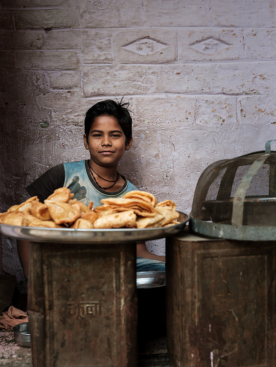 Varanasi, INDIA - CIRCA NOVEMBER 2018: Portrait of kid from a fishing village selling street food close to Varanasi. Varanasi is the spiritual capital of India, the holiest of the seven sacred cities and with that many rituals and offerings are performed daily by priests and hindus.