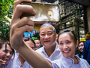 16 JANUARY 2013 - BANGKOK, THAILAND:  SUKHUMBHAND PARIBATRA, candidate for Governor of Bangkok, poses for photos with students during a campaign appearance on Silom Road in Bangkok. The Oxford educated Sukhumbhand is a member of the Thai royal family (he is a great grandson of the late Thai King Chulalongkorn). He is a member of the Thai Democrat party and was first elected Governor of Bangkok in 2009. He is running for reelection this year. Sukhumbhand faces six challengers in the March 3 election. His toughest opponent is expected to be Police General Pongsapat Pongcharoen, who is running under the banner of the Pheu Thai Party, which controls the Prime Minister's office and Parliament.    PHOTO BY JACK KURTZ