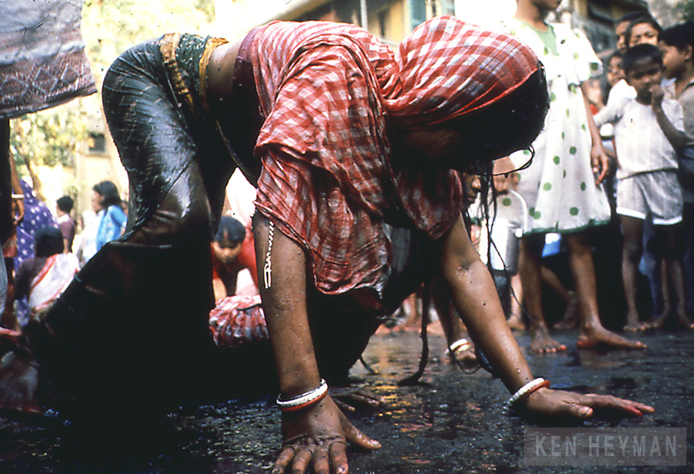 A barren woman crawling in a street in Calcutta in order to become pregnant.