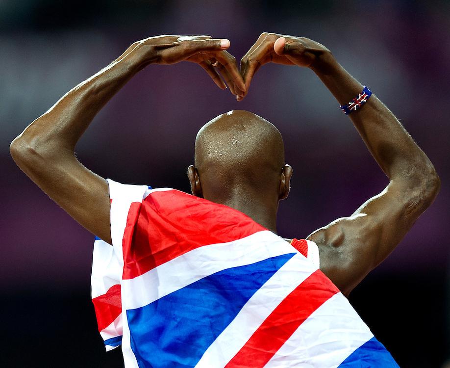 Engeland, Londen, 04-08-2012.<br /> Olympische Spelen.<br /> Atletiek, Mannen, 10.000 meter.<br /> Mo Farah uit Groot Brittannie heeft het goud gewonnen en maakt een groot hart naar het publiek.<br /> Foto : Klaas Jan van der Weij