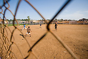 Children playing football on dirt field in Accra, Ghana, 2006.