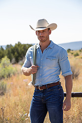 good looking rugged cowboy by a fence on a ranch