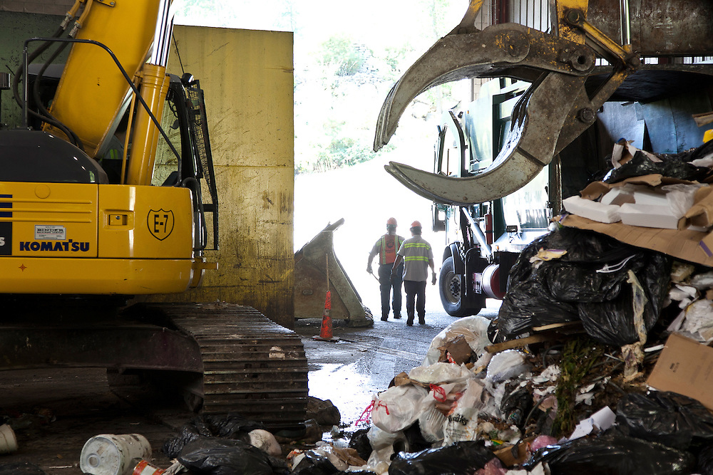 Heavy machinery, men and solid waste at transfer station