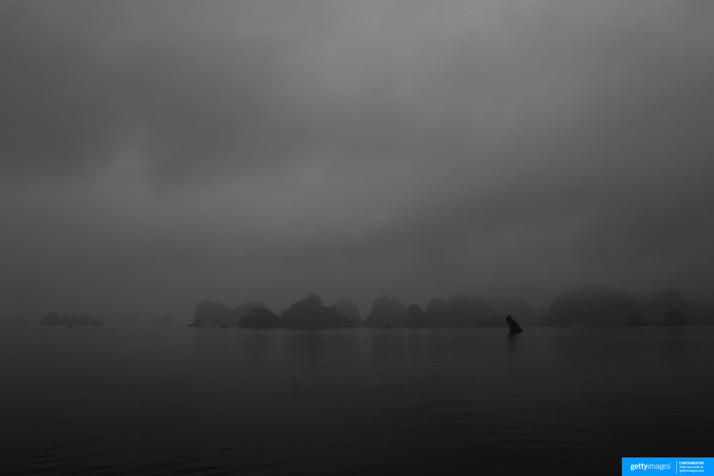 Early morning mist surrounds Ha Long Bay, Vietnam. The bay consists of a dense cluster of 1,969 limestone monolithic islands. Ha Long Bay, is a UNESCO World Heritage Site, and a popular tourist destination. Ha Long, Bay, Vietnam. 11th March 2012. Photo Tim Clayton
