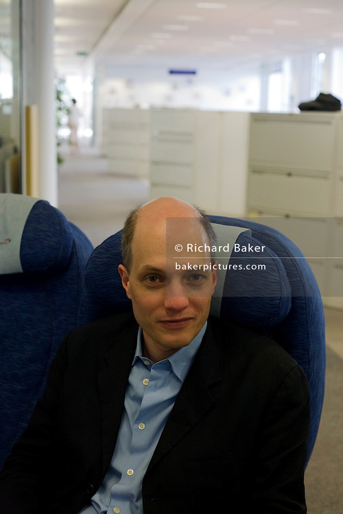 """While working on his book, """"A Week at the Airport: A Heathrow Diary"""" (2009), the writer Alain de Botton's sits in an airline seat at the British Airways' corporate headquarters at Waterside at Harmondsworth near Heathrow Airport."""