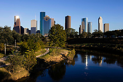 Couple enjoying the Hike & Bike Trail in Buffalo Bayou Park with the downtown Houston skyline in the background.
