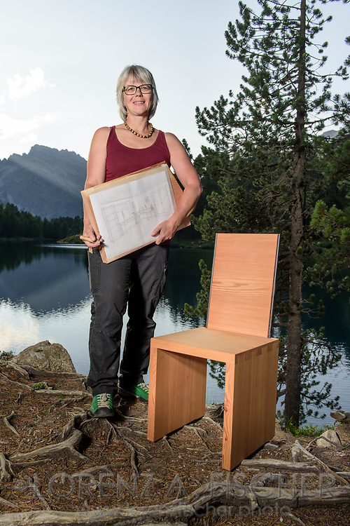 Barbara Schuler with a designed wooden chair with the lake Palpuogna and the Piz Ela and Rugnux in the background on a cloudy summer evening in July, Parc Ela, Grisons, Switzerland