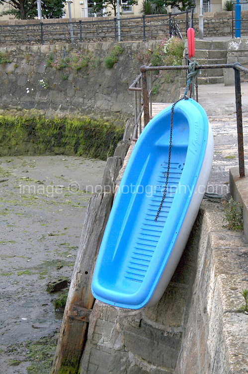 Small plastic boat hanging over the edge of Dun Laoghaire Pier to dry in Dublin Ireland