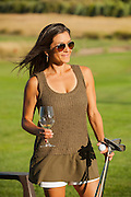 A woman playing golf and wine tasting at Three Rivers Winery