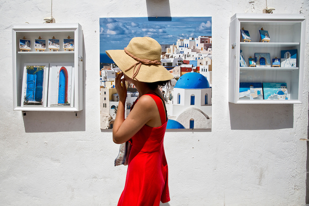 A woman in a red dress and sun hat walks by some typical art on Santorini Island.