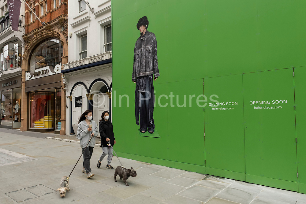 People interact with large scale action figures wearing fashionable clothing against a huge green hoarding which covers the Balenciaga store during a refit in the upmarket area on Bond Street on 25th May 2021 in London, United Kingdom. These high end brands are seen next to each other on a very ordinary wall. Bond Street is one of the principal streets in the West End shopping district and is very upmarket. It has been a fashionable shopping street since the 18th century. The rich and wealthy shop here mostly for high end fashion and jewellery.