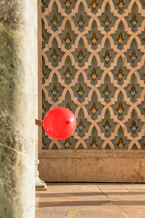 Kid playing with balloon near Hassan II Mosque in Casablanca, Morocco