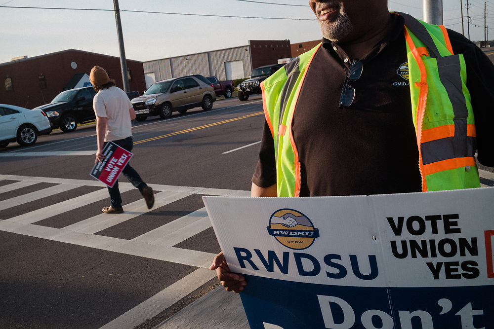 """BESSEMER, AL – MARCH 12, 2021: Curtis Gray (right) canvasses the entrance to the BHM1 Amazon fulfillment warehouse. As visiting agent and vice president of the Retail Wholesale and Department Store Union, Gray has been affiliated with the union for 36 years and feels confident the vote will pass. """"I think we got it, I really do,"""" Gray said. """"Just from the response of the people coming out. Every now and then you get somebody giving a thumbs down, but most people are blowing their horn. This is a union town. It's just a positive attitude from everybody."""" And to be honest, I'm proud to be a black man from Birmingham, and to see a group of people that's 80% black standing up for themselves. That's not happening anywhere else in the country. So win or lose, we've made history already."""" If the unionization effort is successful, BHM1 will become the first unionized Amazon warehouse in the country. CREDIT: Bob Miller for The New York Times"""