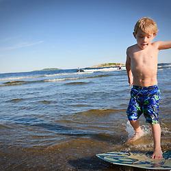 A boy (age 6) skim boarding at Popham Beach State Park in Phippsburg, Maine.