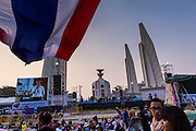 03 JANUARY 2014 - BANGKOK, THAILAND:  An anti-government protestor flies a Thai flag near Democracy Monument in Bangkok. Thousands of Thai anti-government protestors came to Democracy Monument Friday night to hear Suthep Thaugsuban, the leader of the protests, announce his plans to shut down the city of Bangkok. Suthep said his protestors would occupy 20 major intersections in the commercial sections of Bangkok for up to three weeks or until the caretaker government of Yingluck Shinawatra resigns.    PHOTO BY JACK KURTZ