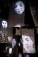 Mons, Belgium. 'Song Lines', a sound installation in Rue de la Poterie, with Tombe la niege chanted and portraits of the singers projected onto sheets and other pieces of cloth suspended above the street. Weekend of inauguration of Mons as European Capital of Culture 2015 (24 January 2015). © Rudolf Abraham