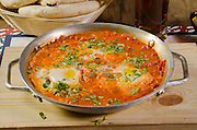 Shakshuka (Also Shakshouka, shakshoka, chakchouka) an Israeli dish made of cooked tomatoes, peppers, spices and eggs