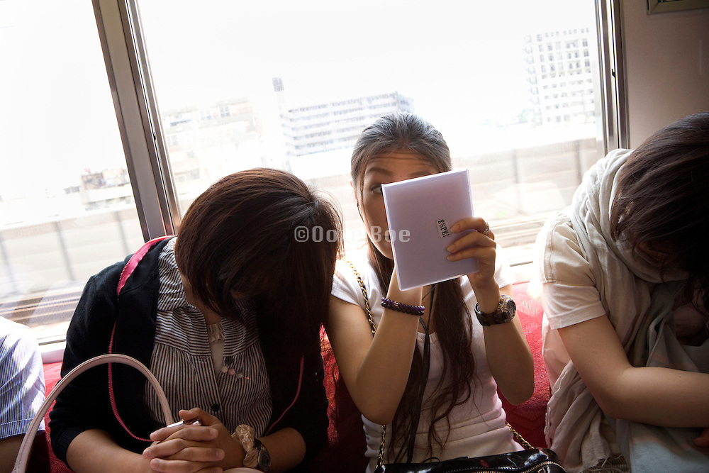Japanese girl doing her make up while sitting in a train with other girls sleeping