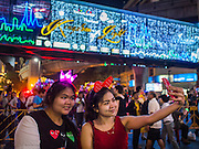 "31 DECEMBER 2014 - BANGKOK, THAILAND:  Women take a ""selfie"" under the lights at the New Year's party in Rathaprasong. Hundreds of thousands of people pack into the Ratchaprasong Intersection in Bangkok for the city's annual New Year's Eve countdown. Many Thais go the Erawan Shrine and Wat Pathum Wanaram near the intersection to pray and make merit before going to their New Year's parties.   PHOTO BY JACK KURTZ"