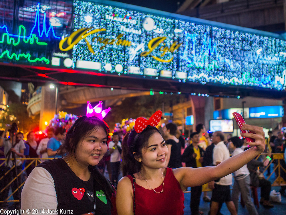 """31 DECEMBER 2014 - BANGKOK, THAILAND:  Women take a """"selfie"""" under the lights at the New Year's party in Rathaprasong. Hundreds of thousands of people pack into the Ratchaprasong Intersection in Bangkok for the city's annual New Year's Eve countdown. Many Thais go the Erawan Shrine and Wat Pathum Wanaram near the intersection to pray and make merit before going to their New Year's parties.   PHOTO BY JACK KURTZ"""