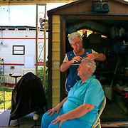 Barb Dossett combs Pat Worley's hair while giving her a cut and a perm outside her winter home at Citrus Valley RV Park in McAllen. Dossett, an 11th year winter Texan from Illinois, arrived back in the Rio Grande Valley on Friday. Worley, who was born and raised in the valley, said she waited for six months to Dossett to return and perm her hair. <br /> Nathan Lambrecht/The Monitor
