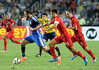 Gonzalo Higuain of Argentina, left, breaks through Andy Nagelein, right, and Chan Wai-ho, second right, of Hong Kong during a friendly football match in Hong Kong, China, 14 October 2014.<br /> <br /> Lionel Messi needed just six minutes to make his mark in Argentina's 7-0 rout of Hong Kong in a friendly at Hong Kong Stadium on Tuesday (14 October 2014). The Barcelona star Messi scored twice after going on as a substitute for the last 30 minutes of the game to celebrate the 100th anniversary of the Hong Kong Football Association. Napoli striker Gonzalo Higuain and Benfica's Nicolas Gaitan also scored two goals each after Sevilla's Ever Banega had opened scoring in the 19th minute.