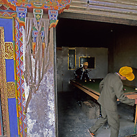 Boys play pool in a shop next to traditional, ornate door in a village in the Lunang Valley of Tibet, China.