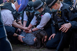 © Licensed to London News Pictures. 27/02/2021. London, UK. Police officers arrest a woman attending an anti-vaccination and anti-lockdown demonstration in Bishops Park area of Fulham, West London. The group  against the current tier regulations and anti-vaccination for the Covid-19 disease credit: Ray Tang/LNP