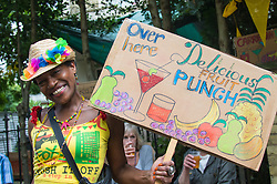 "London, August 29th 2016. A woman advertises her ""delicious fruit punch"" during day two of Europe's biggest street party, the Notting Hill Carnival."