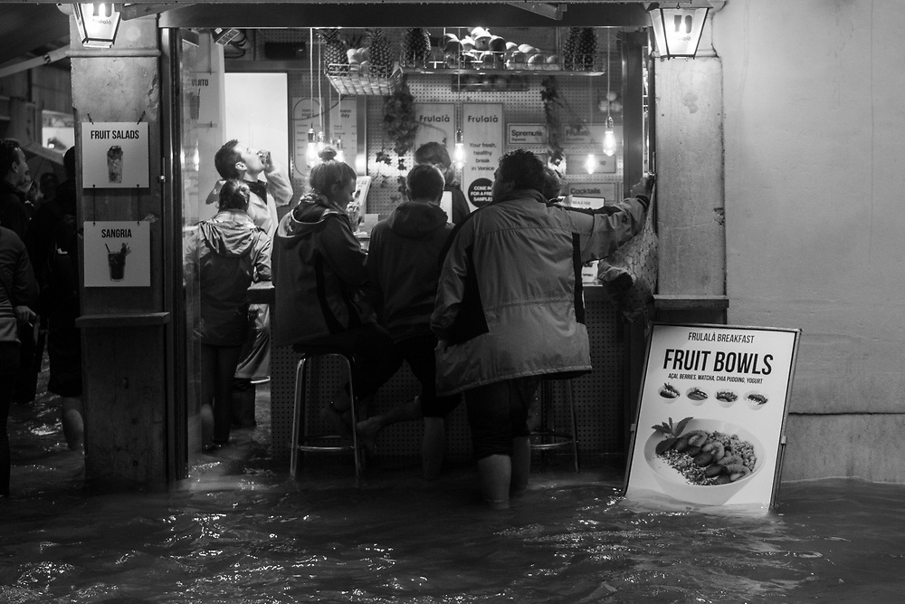 Venice, Italy. 29 October, 2018.  Citizens and tourists drink in a bar wearing boots during the high tide in San Marco district on October 29, 2018, in Venice, Italy. This is a selection of pictures of different areas of Venice that the press has not covered, were resident live and every year they have to struggle with the high tide. Due to the exceptional level of the 'acqua alta' or 'High Tide' that reached 156 cm today, Venetian schools and hospitals were closed by the authorities, and citizens were advised against leaving their homes. This level of High Tide has been reached in 1979. © Simone Padovani / Awakening / Alamy Live News