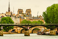 People jogging on the Pont des Arts across the Seine River (with Notre Dame Cathedral in background), Paris, France.