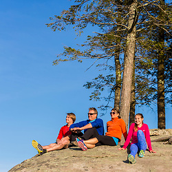 A couple and their teenage son and daughter relaxing on the summit of Mount Agamenticus in York, Maine.