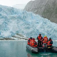 Adventure travelers in a zodiac raft float below a glacier icefall in the Cordillera Darwin that flows into Seno Chico, a small fjord in Alberto De Agostini National Park, Tierra del Fuego, Chile.