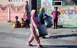 """South Africa - Cape Town - 17 June 2020 - Girls helping carry huge pots as Mosadie Givesback who is preparing for Mandela Day with in Mitchells Plain after having given those in need their porridge for the morning. Picture"""" Brendan Magaar/African News Agency(ANA)"""