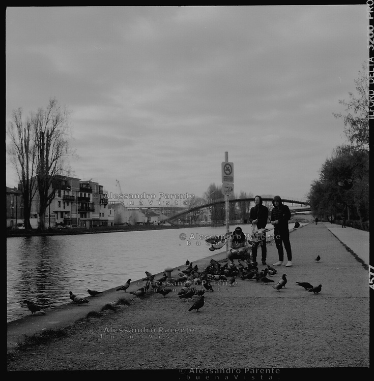 Aubervilliers,Seine Saint Denis. People giving food to pigeons in the canal.